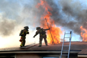 Firefighters on a Roof Putting Out a Nearby Fire